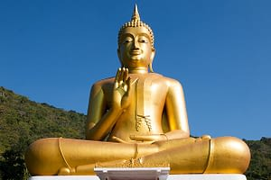 Picture of a large Golden Buddha statue standing powerfully against a deep blue sky