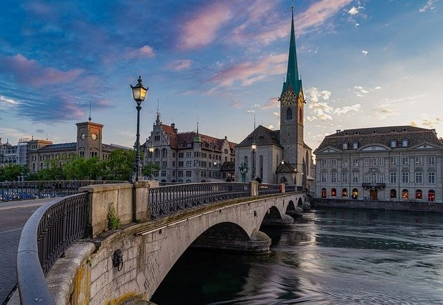 Picture a stone bridge leading to steepled architecture in Zurich Switzerland