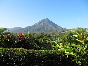 Picture of a tropical garden with Mount Arenol and a bright blue sky in the background