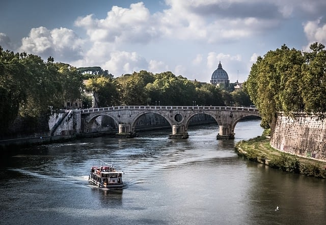 Picture of the waterway in Rome heading for an arched brick bridge