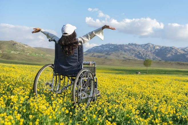 A young girl, sitting in a wheelchair in a field of flowers celebrates life.