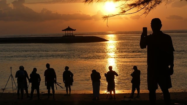 People line the edge of the water for pictures of the stunning Balinese sunrise